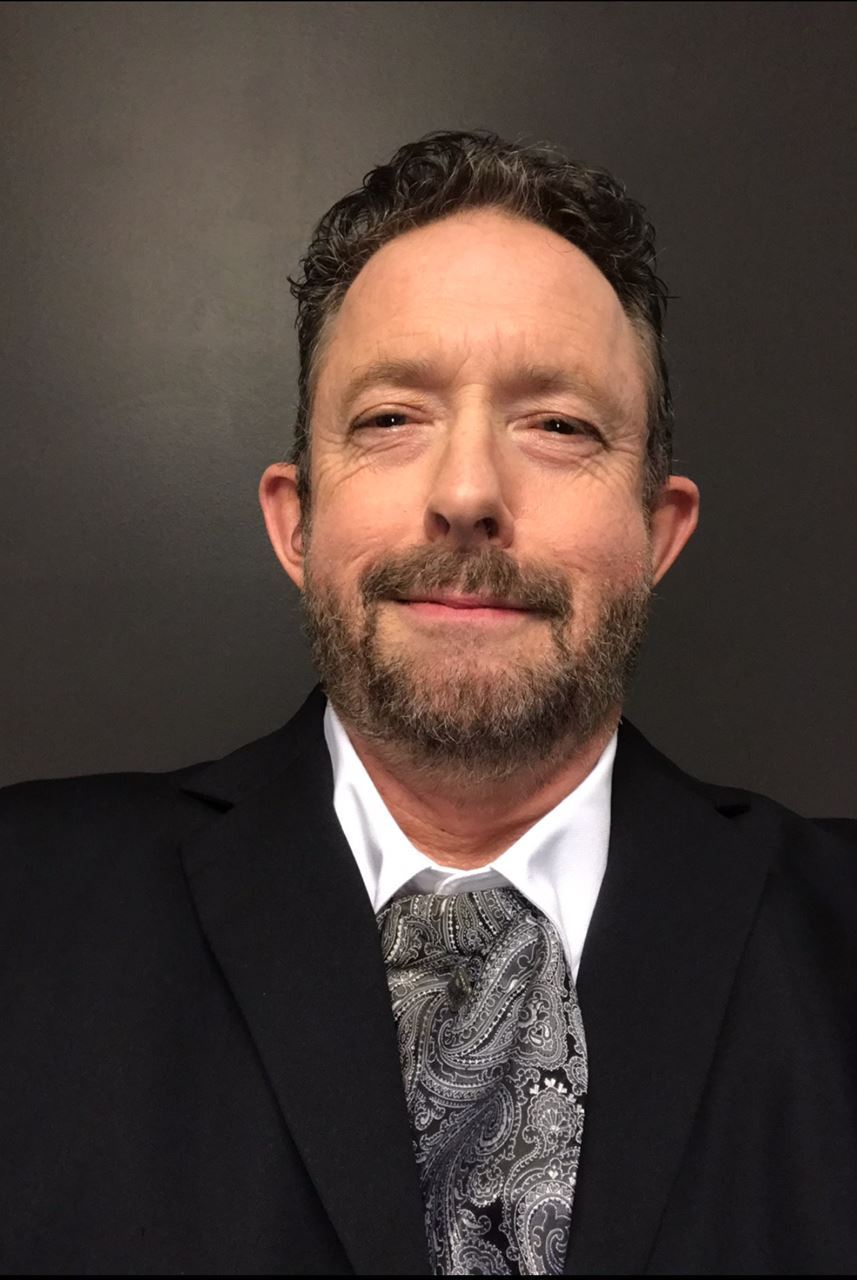 [image description A portrait of Matt Moyers, a white male with a beard, mustache, and short brown hair. He is wearing a dark suit jacket, white collared shirt and paisley patterned black ascot. He is posing in front of a dark gray background.]