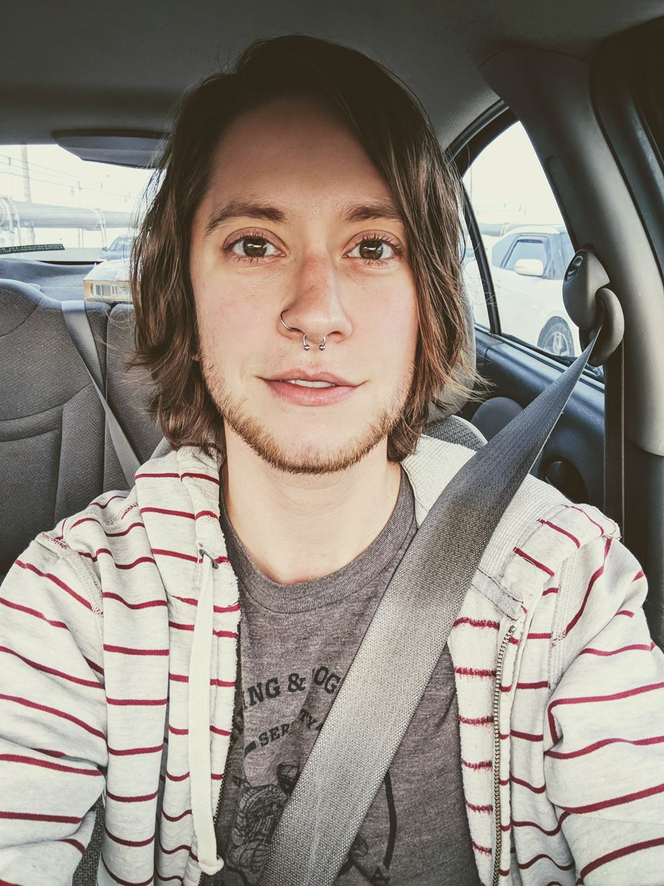 [image description Selfie of Reid. They are sitting in a car with a seatbelt on. They are white, have medium length brown hair, hazel eyes, and a short beardchin strap. They have a hoop in their right nostril and a horseshoe ring in their septum. They are wearing a brown shirt under an unzipped hoodie that is grey with narrow maroon stripes. They are staring at the camera and their mouth is open in a slight smile. It is daytime and another car is visible in the background.]
