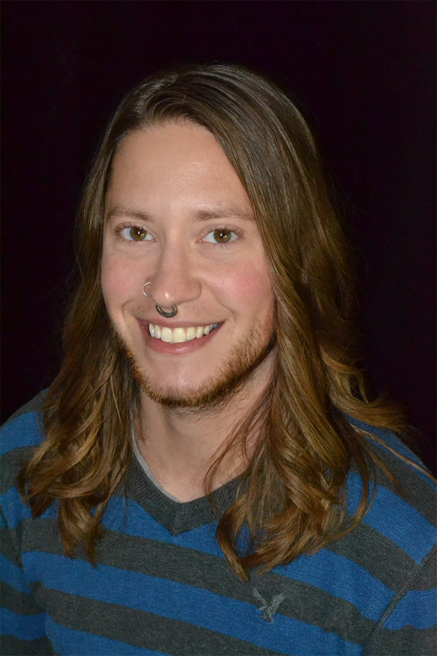 Head shot style photo of Reid, they are smiling at the camera and wearing a blue and grey striped sweater in front of a black background. They are a white person with long brown hair past their shoulders and short facial hair. They have a septum ring and a nose ring.